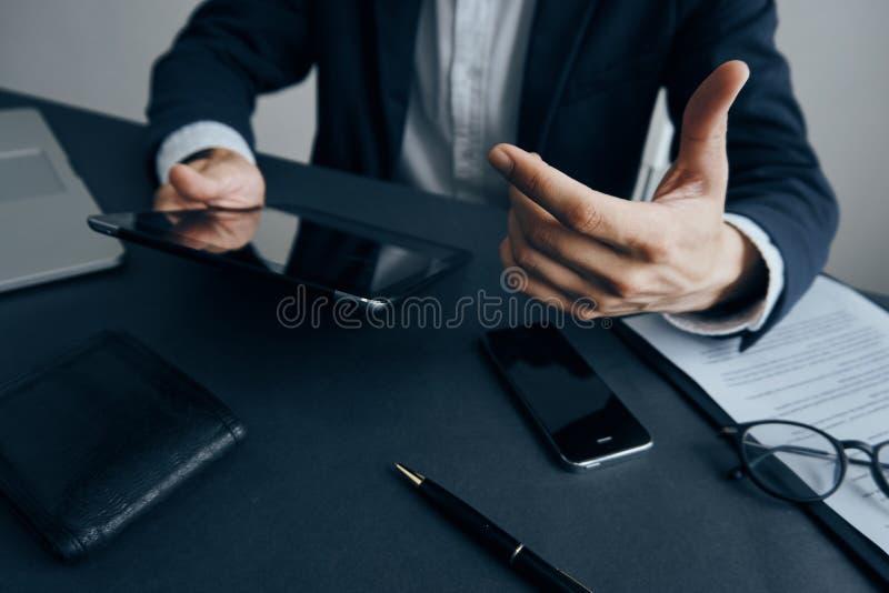 Bedrijfsmens met een baard die een tablet in het bureau houden bij zijn bureau stock afbeelding
