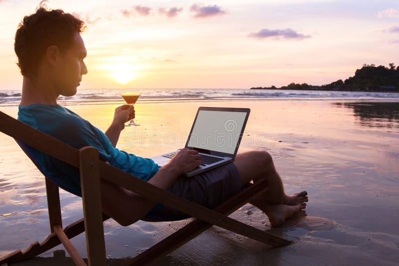 Bedrijfsmens met laptop op het strand royalty-vrije stock afbeelding