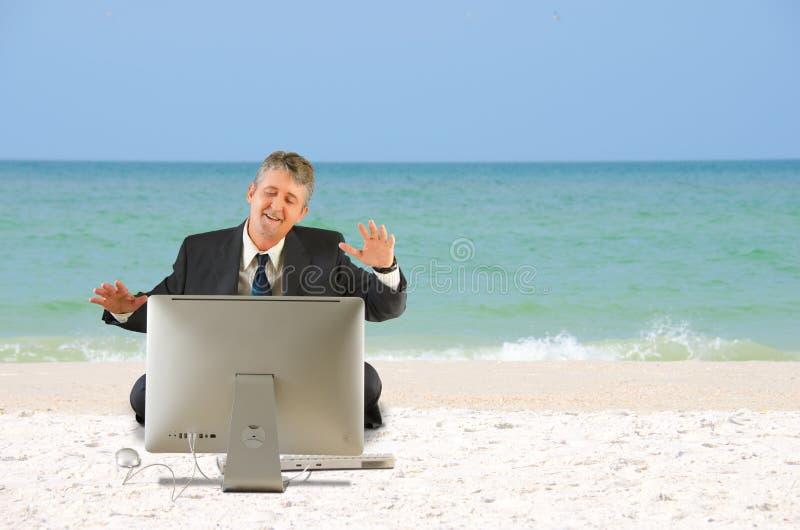 Bedrijfsmens op het strand met een computer stock foto's