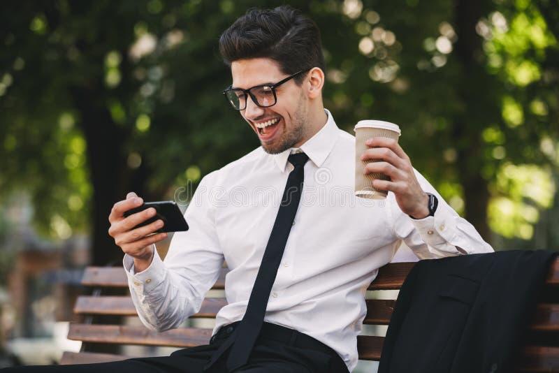 Bedrijfsmens in openlucht in de spelen van het parkspel door telefoon het drinken koffie stock afbeelding
