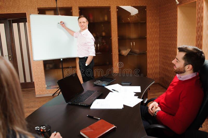 Bedrijfsmensen in bureau die een conferentie houden en strategieën bespreken stock afbeelding