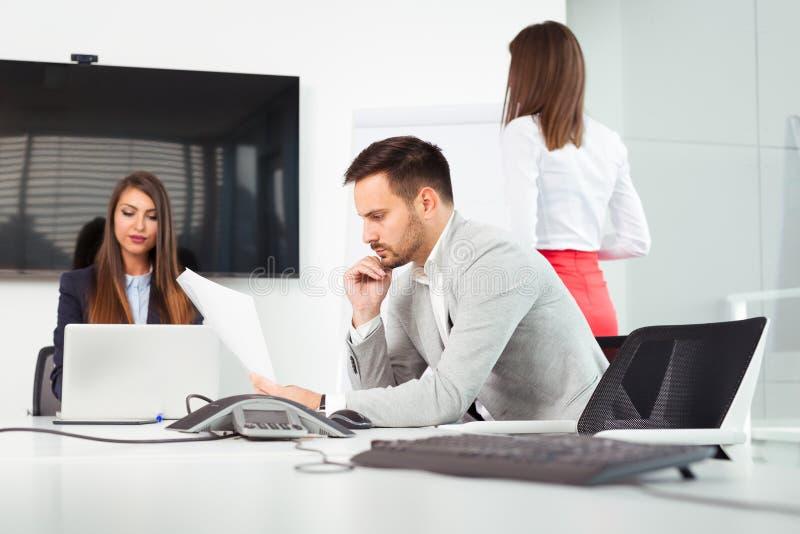 Bedrijfsmensen in bureau die een conferentie houden en strategieën bespreken stock fotografie