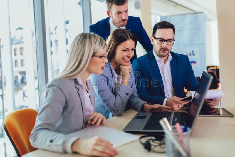 Bedrijfsmensen die aan bedrijfsproject in bureau werken die laptop met behulp van stock foto
