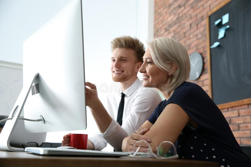 Bedrijfsmensen die aan computer bij lijst in bureau werken stock afbeeldingen