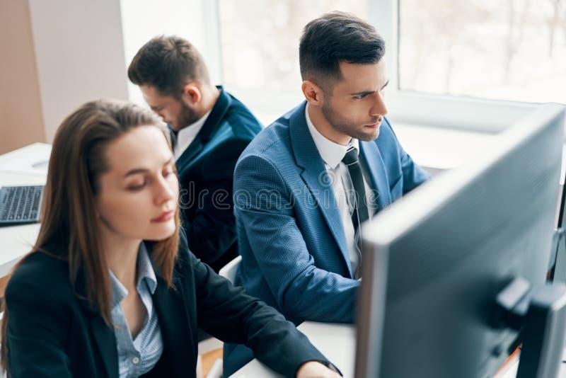 Bedrijfsmensen die aan computer in zijn werkplaats werken stock afbeelding