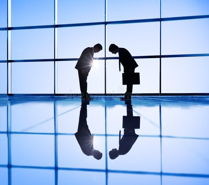 Bedrijfsmensen die aan elkaar buigen stock foto's