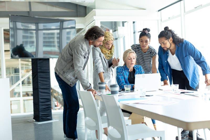 Bedrijfsmensen die aan laptop bij conferentieruimte samenwerken in een modern bureau stock foto