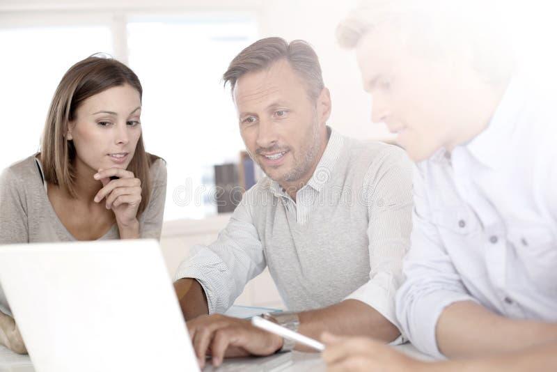 Bedrijfsmensen die aan project met laptop werken stock foto's
