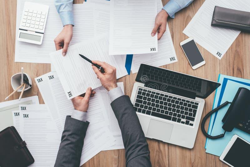 Bedrijfsmensen die belastingsvormen controleren royalty-vrije stock afbeelding
