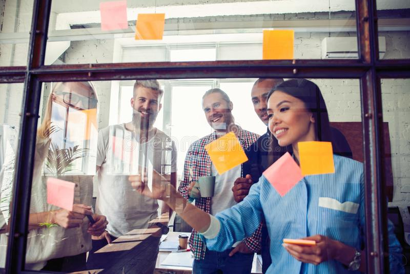 Bedrijfsmensen die bij bureau en gebruikspost-itnota's samenkomen om idee te delen Hersenen en flitsen Kleverige nota over glasmu royalty-vrije stock foto