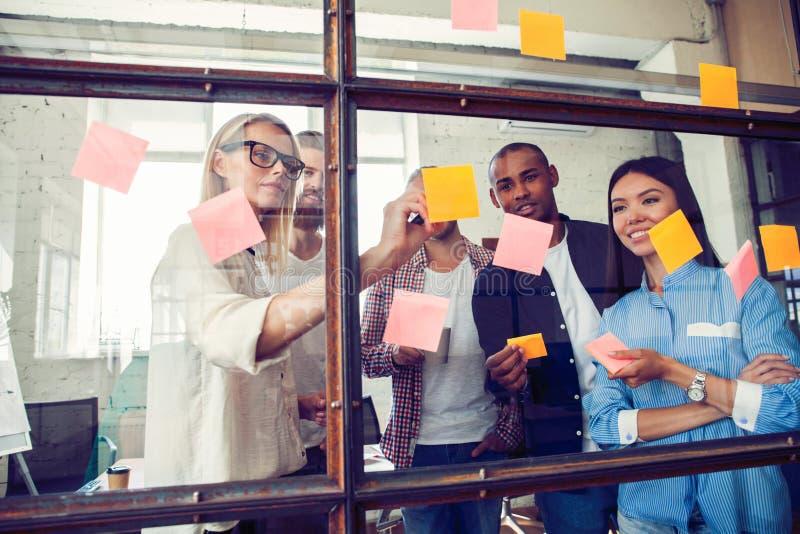 Bedrijfsmensen die bij bureau en gebruikspost-itnota's samenkomen om idee te delen Hersenen en flitsen Kleverige nota over glasmu stock afbeelding