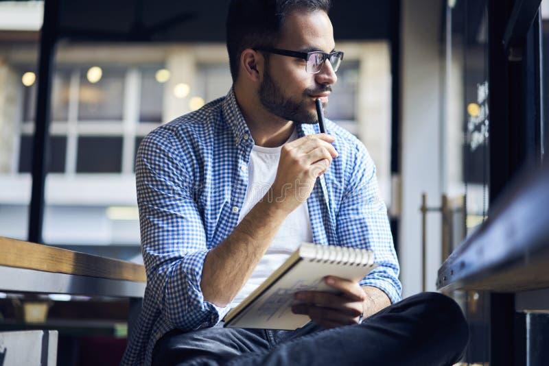 Bedrijfsmensen die in blauw overhemd grafische uitgave voor flatbinnenland creëren in notitieboekje royalty-vrije stock afbeelding