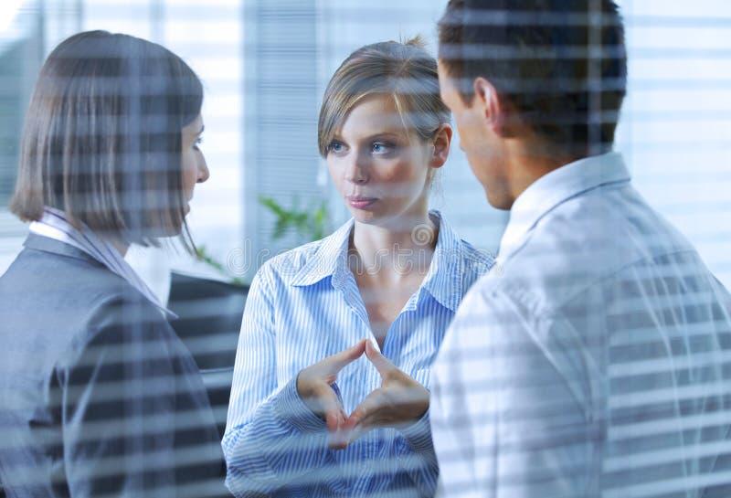 Bedrijfsmensen die in Bureau converseren stock afbeelding