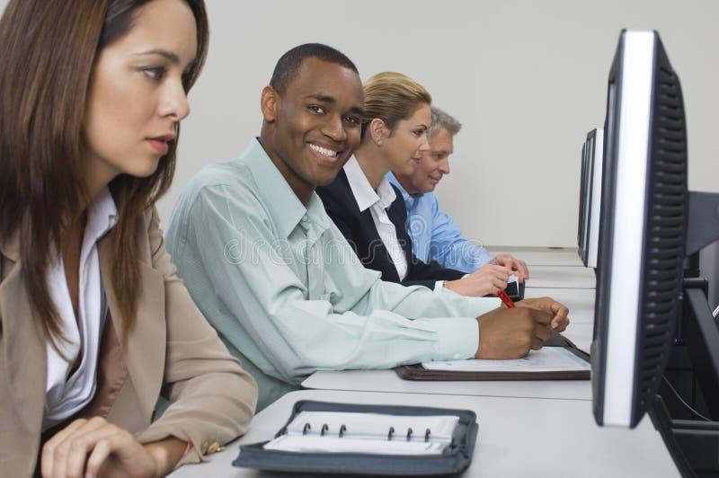 Bedrijfsmensen die Computers in Klaslokaal met behulp van royalty-vrije stock afbeelding