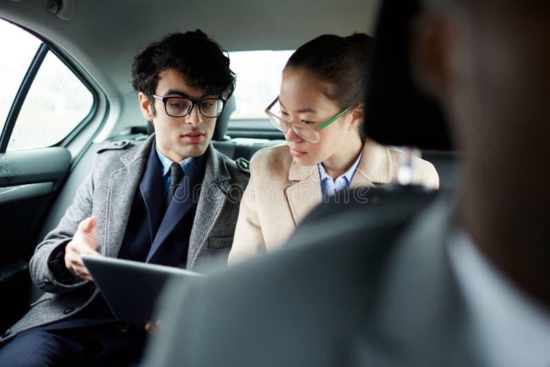 Bedrijfsmensen die Document in Auto bespreken stock afbeelding
