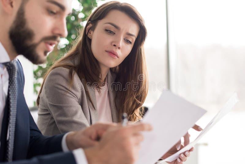 Bedrijfsmensen die Documenten in Bureau bespreken stock fotografie