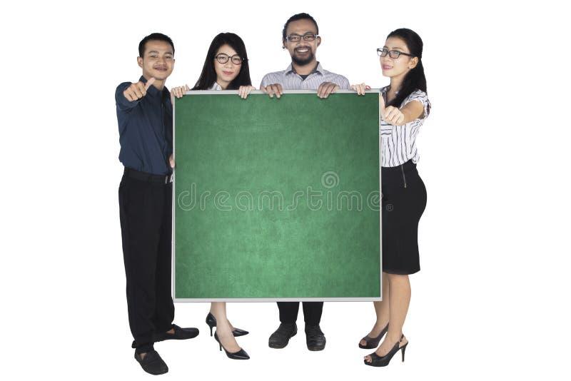 Bedrijfsmensen die duimen en bord tonen stock foto