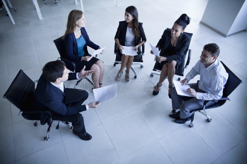Bedrijfsmensen die in een cirkel zitten die een commerciële vergadering hebben stock afbeeldingen