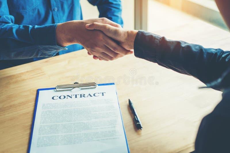 Bedrijfsmensen die een contracthanddruk tussen col. twee bespreken royalty-vrije stock afbeeldingen