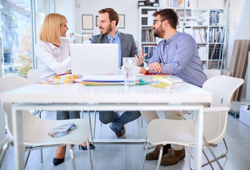 Bedrijfsmensen die en in bureau samenwerken communiceren royalty-vrije stock foto's