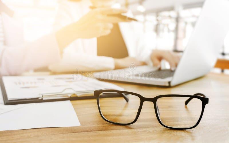 Bedrijfsmensen die en op commerciële vergadering zitten bespreken, in bureau, geselecteerde nadruk op oogglazen stock fotografie
