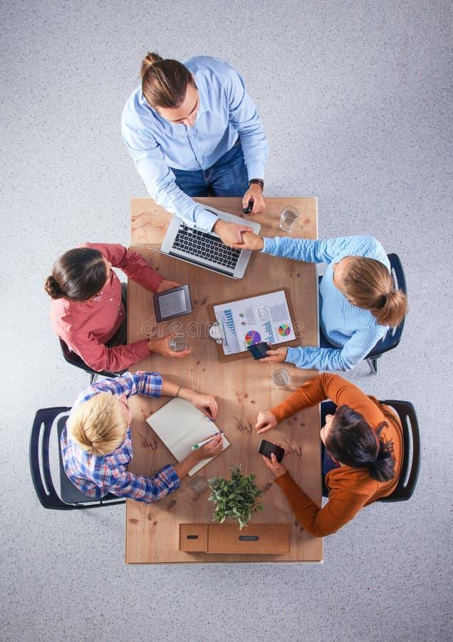 Bedrijfsmensen die en op vergadering, in bureau zitten bespreken stock foto