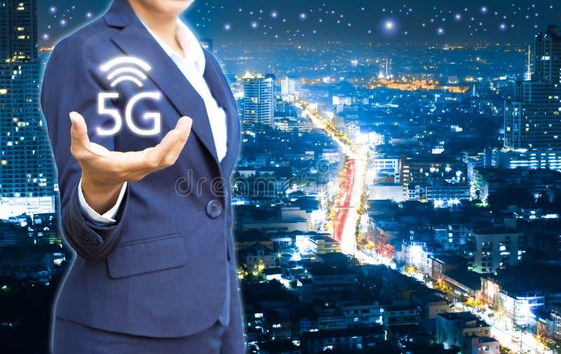Bedrijfsmensen die 5g-radio op stad tonen bij de nachtachtergrond stock foto