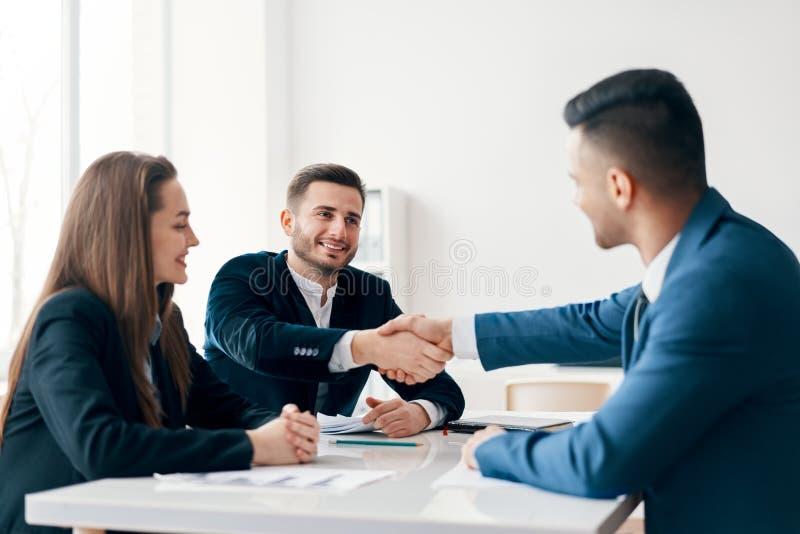 Bedrijfsmensen die handen na goede overeenkomst schudden stock foto