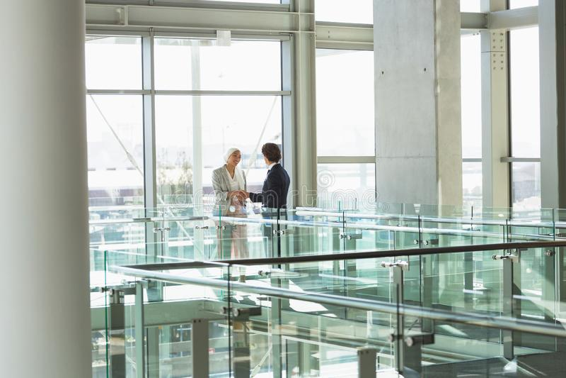 Bedrijfsmensen die handen samen in gang schudden op modern kantoor stock afbeeldingen