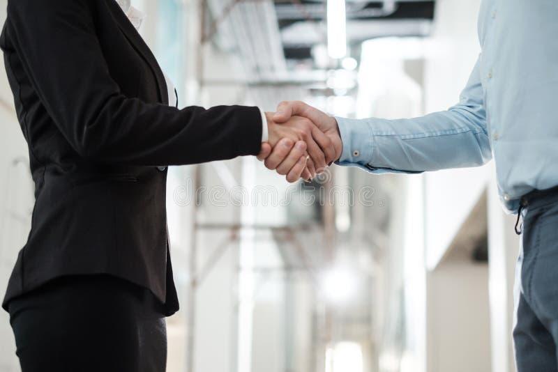 Bedrijfsmensen die handen schudden als teken van overeenkomst stock foto's