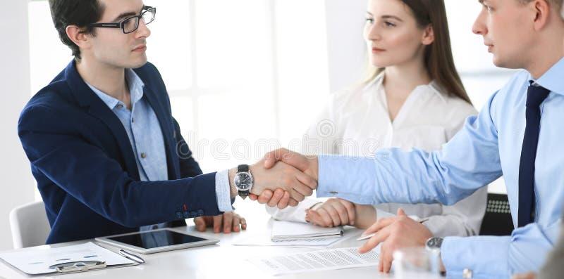Bedrijfsmensen die handen schudden bij vergadering of onderhandeling Groep zakenlieden en vrouwen in modern bureau groepswerk royalty-vrije stock foto's