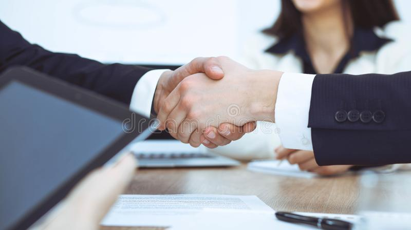 Bedrijfsmensen die handen schudden bij vergadering of onderhandeling in het bureau Handdrukconcept De partners zijn tevreden omda royalty-vrije stock fotografie