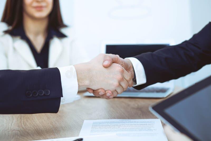 Bedrijfsmensen die handen schudden bij vergadering of onderhandeling in het bureau Handdrukconcept De partners zijn tevreden omda royalty-vrije stock afbeeldingen