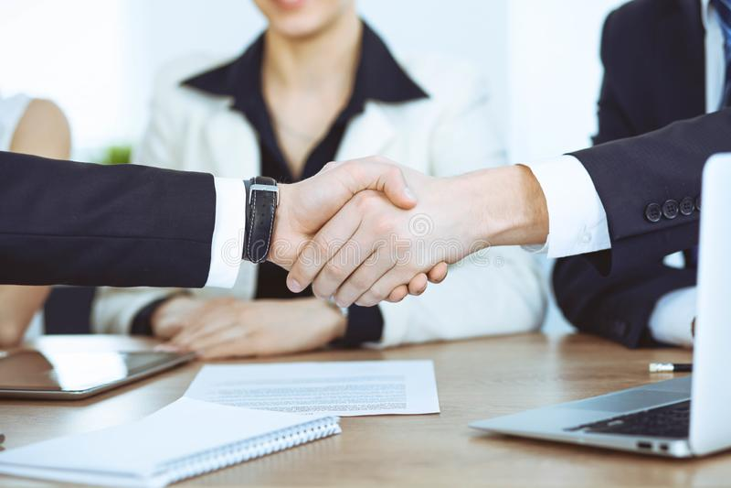 Bedrijfsmensen die handen schudden bij vergadering of onderhandeling in het bureau Handdrukconcept De partners zijn tevreden omda royalty-vrije stock afbeelding
