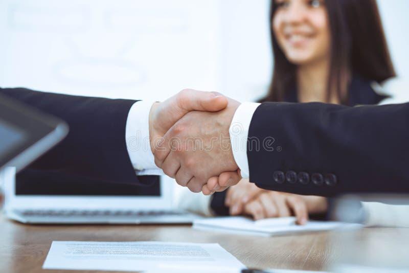 Bedrijfsmensen die handen schudden bij vergadering of onderhandeling in het bureau Handdrukconcept De partners zijn tevreden omda royalty-vrije stock foto's