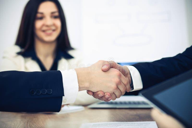 Bedrijfsmensen die handen schudden bij vergadering of onderhandeling in het bureau Handdrukconcept De partners zijn tevreden omda stock foto