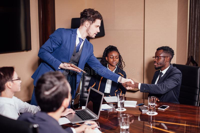 Bedrijfsmensen die handen schudden, die omhoog een vergadering beëindigen stock foto