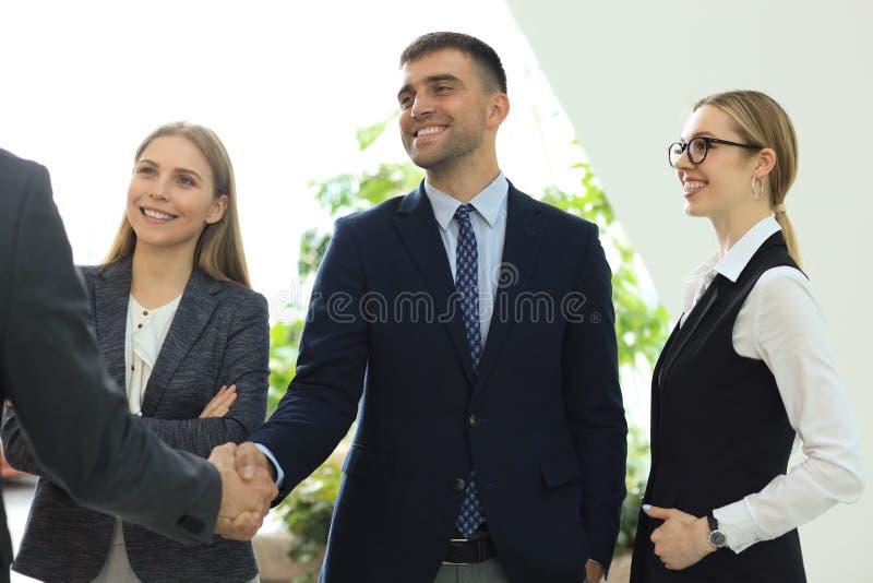 Bedrijfsmensen die handen schudden, die omhoog een vergadering be?indigen royalty-vrije stock afbeelding