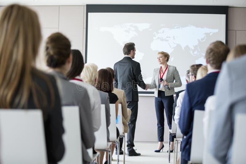 Bedrijfsmensen die handen schudden tijdens seminarie op overeenkomstcentrum royalty-vrije stock foto's