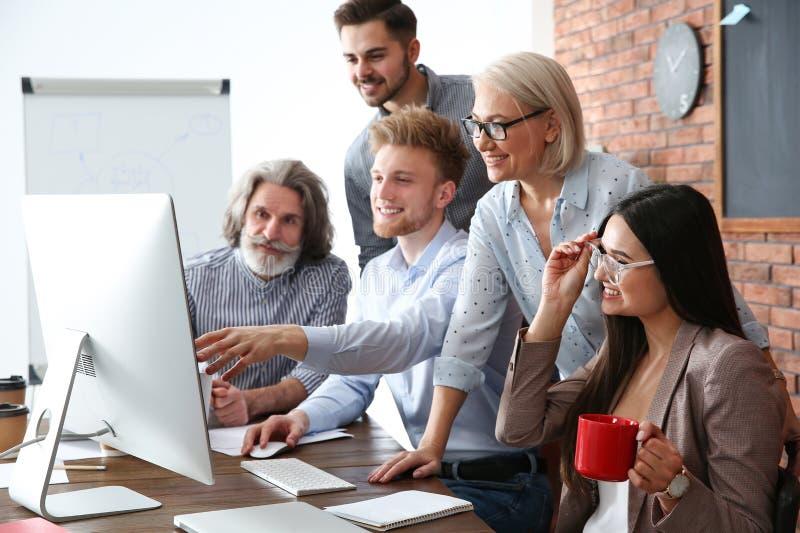Bedrijfsmensen die het werkkwesties bespreken bij lijst in bureau royalty-vrije stock afbeeldingen