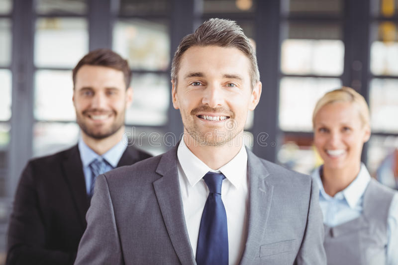 Bedrijfsmensen die kostuum dragen die zich in bureau bevinden royalty-vrije stock foto