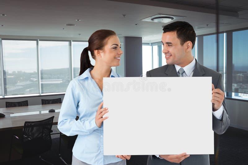 Bedrijfsmensen die lege kaart in bureau houden royalty-vrije stock afbeeldingen