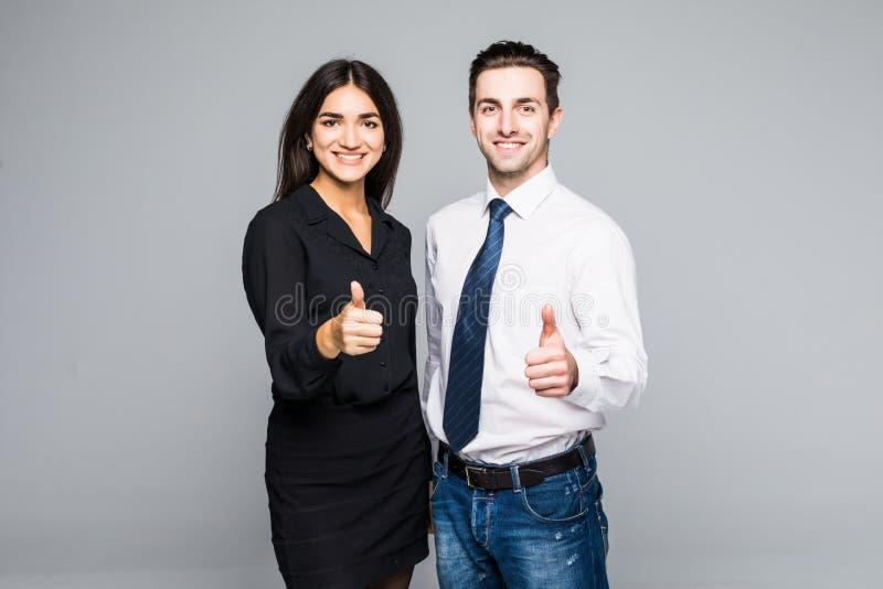 Bedrijfsmensen die omhoog hun duimen op grijze achtergrond hebben royalty-vrije stock foto's