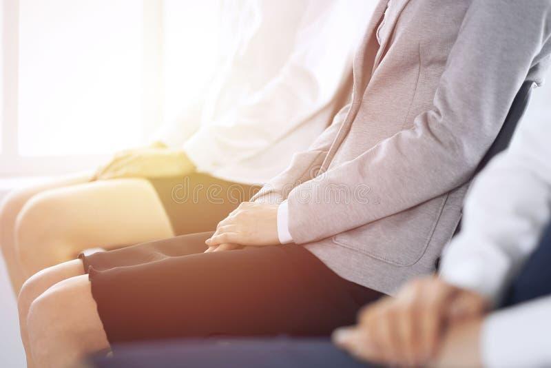 Bedrijfsmensen die op baangesprekken wachten of op conferentie aan bureau deelnemen, close-up Vrouwen die op stoelen zitten royalty-vrije stock fotografie