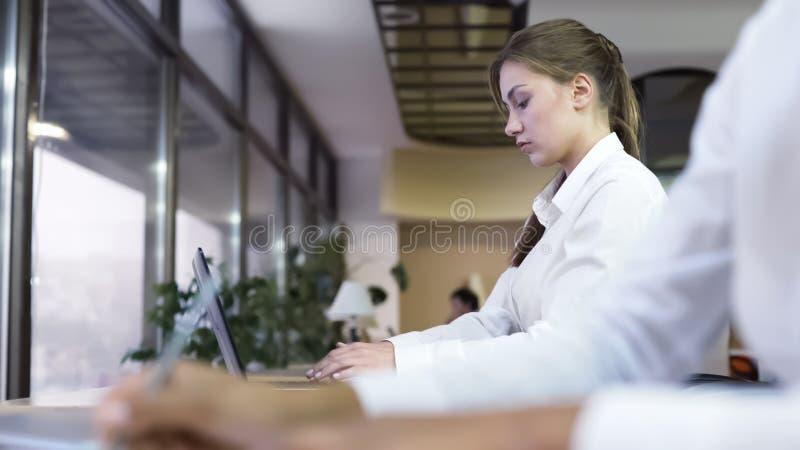 Bedrijfsmensen die op kantoor, aantrekkelijk vrouw het typen rapport werken over laptop stock fotografie