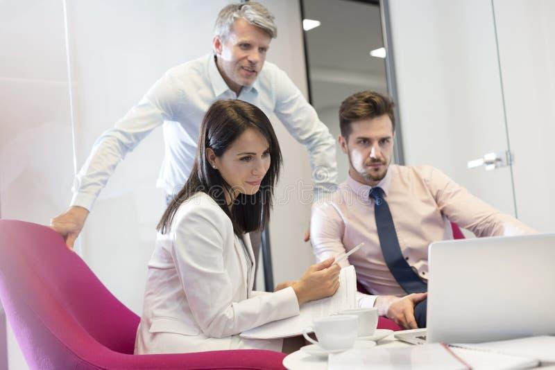Bedrijfsmensen die op laptop in vergadering letten op kantoor royalty-vrije stock foto