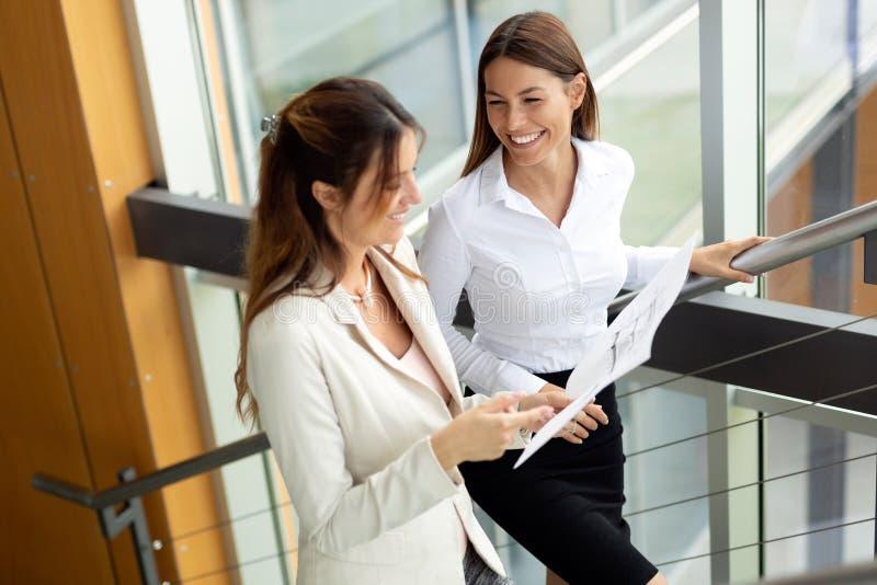 Bedrijfsmensen die over documenten in bureauhal bespreken royalty-vrije stock afbeelding
