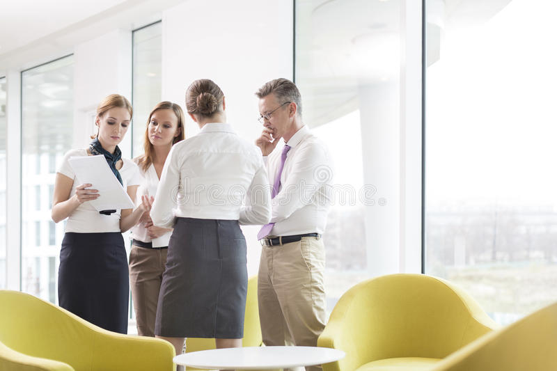 Bedrijfsmensen die over documenten in bureauhal bespreken stock fotografie