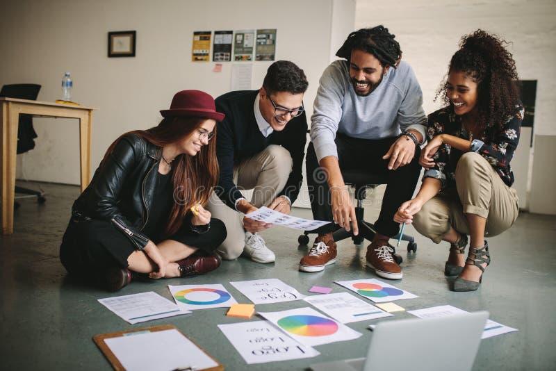 Bedrijfsmensen die plannen bespreken zittend op vloer met documenten stock afbeelding