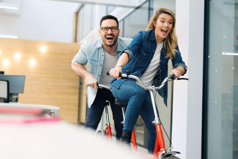 Bedrijfsmensen die pret hebben die een fiets berijden stock fotografie